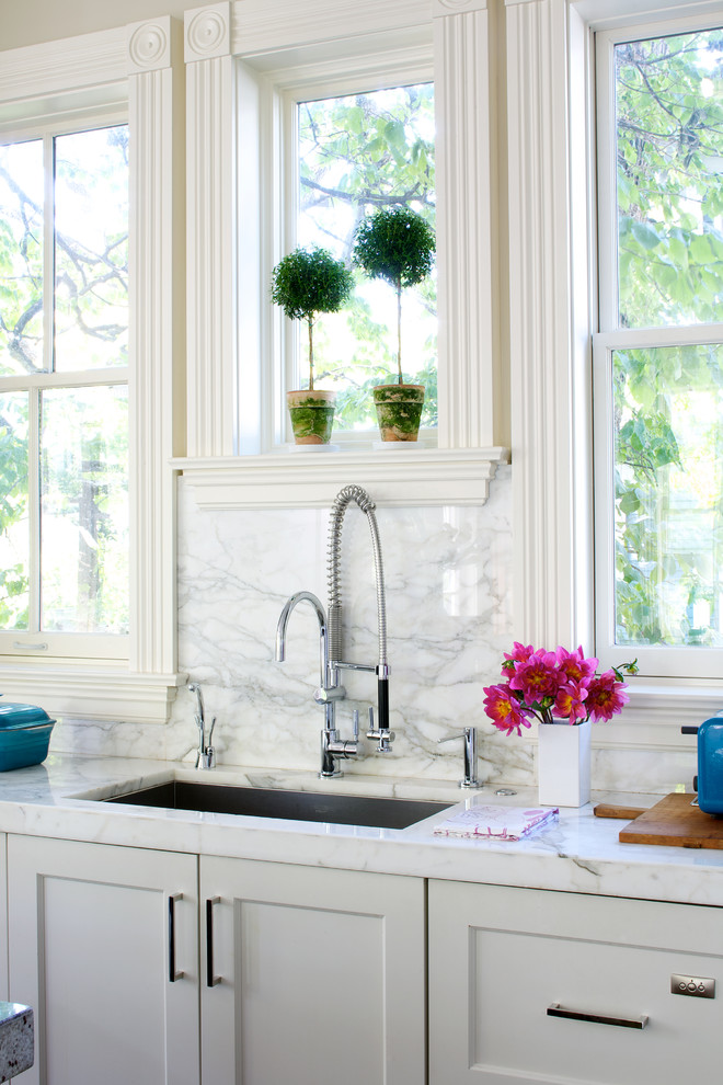 Inspiration for a timeless kitchen remodel in Chicago with recessed-panel cabinets, an undermount sink, white cabinets, white backsplash and stone slab backsplash