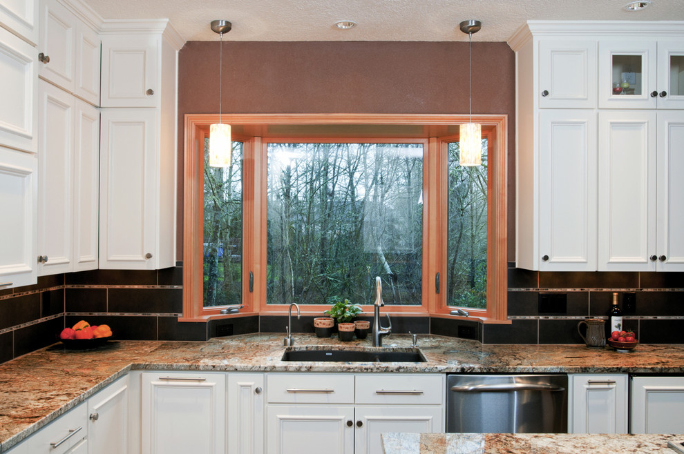 Open concept kitchen - traditional u-shaped open concept kitchen idea in Other with an undermount sink, granite countertops, flat-panel cabinets, white cabinets, brown backsplash, porcelain backsplash and stainless steel appliances