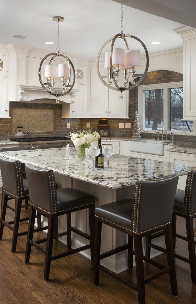 Kitchen - traditional l-shaped dark wood floor kitchen idea in Columbus with a farmhouse sink, shaker cabinets, white cabinets, gray backsplash, subway tile backsplash and an island