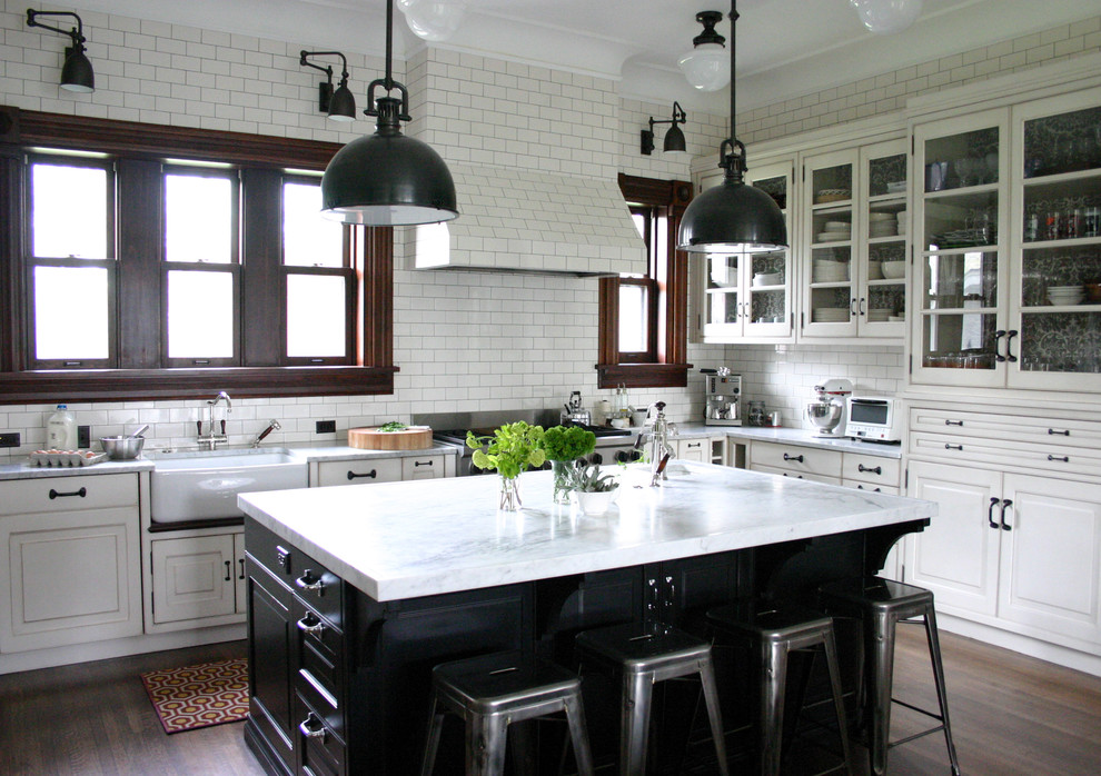 Kitchen - traditional kitchen idea in Chicago with glass-front cabinets, stainless steel appliances, a farmhouse sink, white cabinets, marble countertops, white backsplash, subway tile backsplash and white countertops