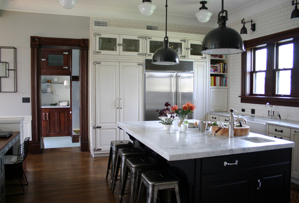 Inspiration for a timeless kitchen remodel in Chicago with glass-front cabinets, subway tile backsplash, a farmhouse sink, white cabinets, white backsplash, stainless steel appliances and marble countertops