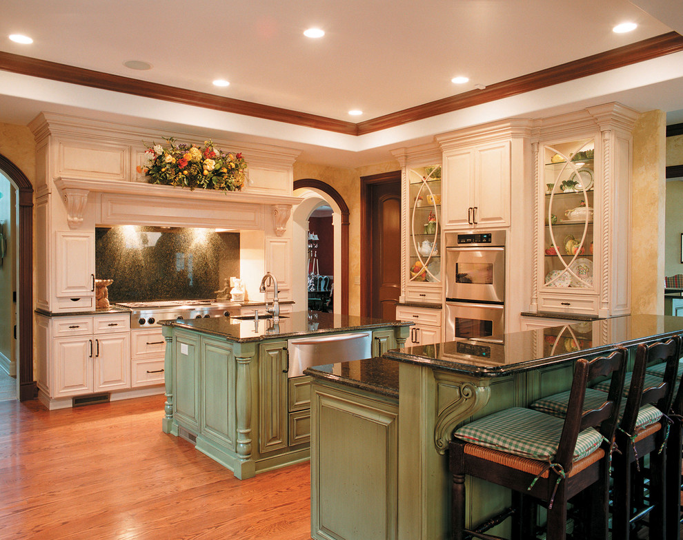 Kitchen - traditional kitchen idea in Other with raised-panel cabinets, stainless steel appliances, green cabinets, black backsplash and stone slab backsplash