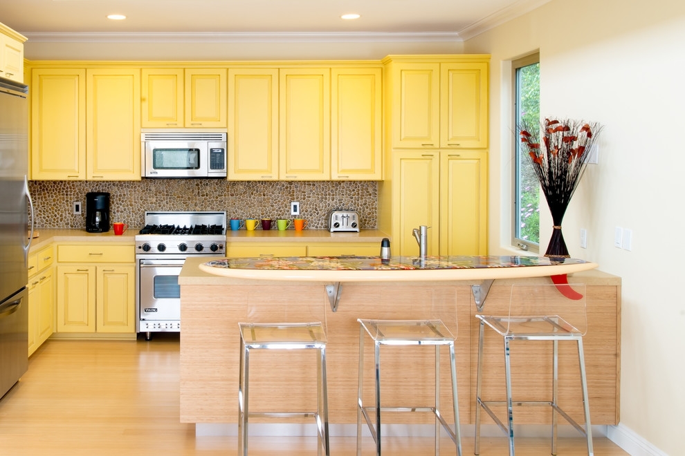 Kitchen - traditional l-shaped light wood floor kitchen idea in Los Angeles with raised-panel cabinets, yellow cabinets, stainless steel appliances and a peninsula