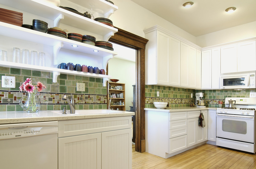 Mid-sized elegant l-shaped light wood floor enclosed kitchen photo in Other with white appliances, open cabinets, white cabinets, green backsplash, an undermount sink, ceramic backsplash and no island