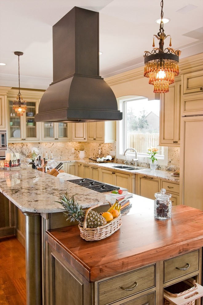 Inspiration for a timeless galley kitchen remodel in Other with beaded inset cabinets, granite countertops, a double-bowl sink, beige cabinets, beige backsplash, stone slab backsplash and paneled appliances