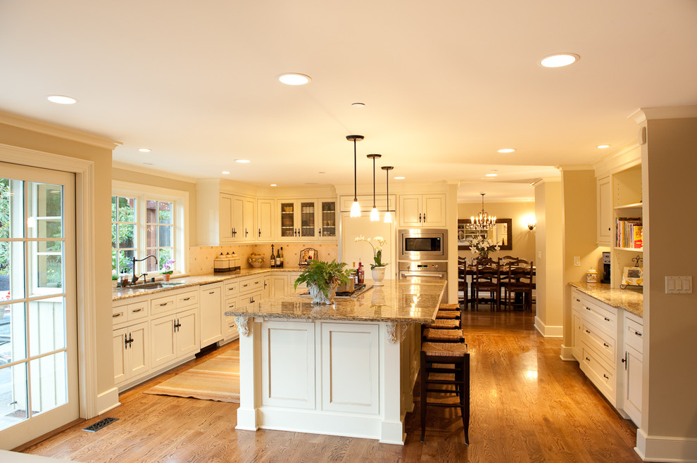 Kitchen - traditional l-shaped medium tone wood floor kitchen idea in Seattle with granite countertops, recessed-panel cabinets, white cabinets, paneled appliances, an undermount sink, white backsplash, ceramic backsplash and an island
