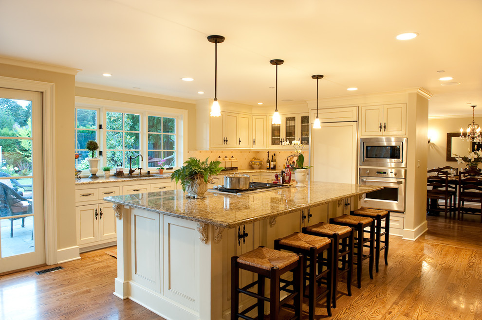 Example of a mid-sized classic l-shaped medium tone wood floor open concept kitchen design in Seattle with beige cabinets, beige backsplash, paneled appliances, ceramic backsplash and an island