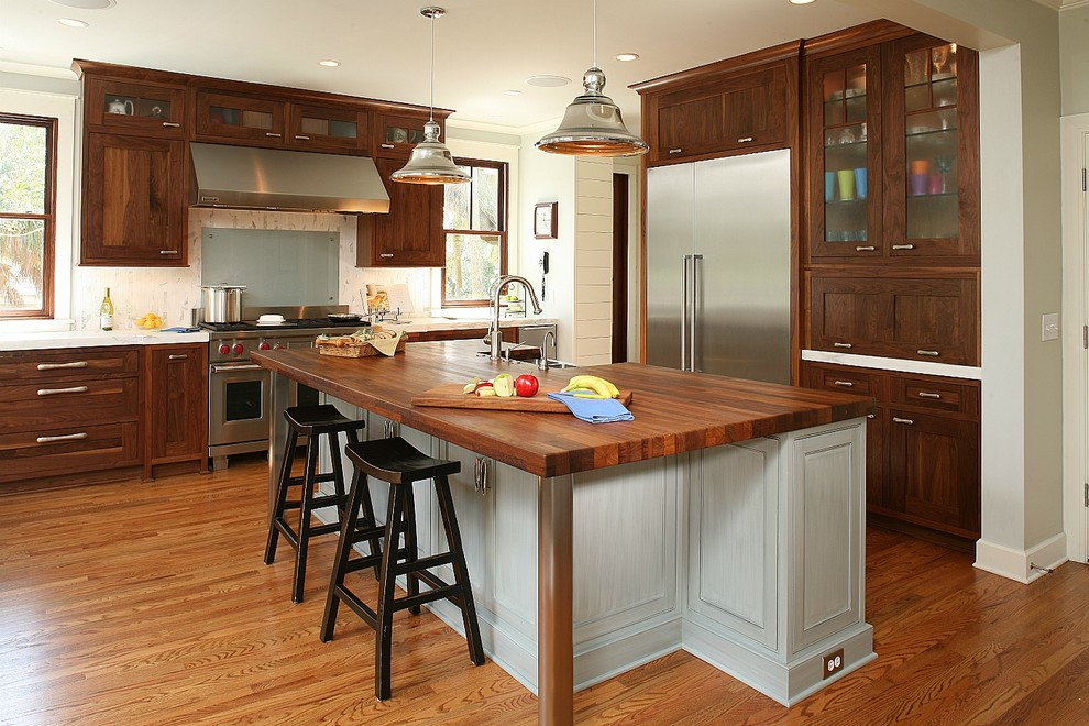 Example of a classic kitchen design in Charleston with glass-front cabinets, stainless steel appliances and wood countertops
