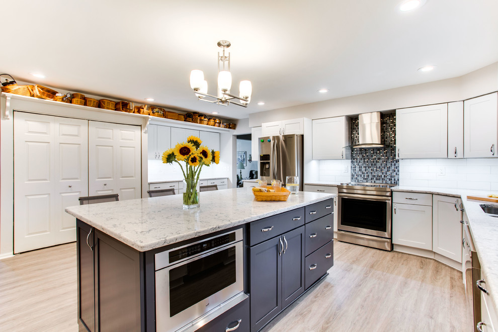 Mid-sized elegant kitchen photo in DC Metro with an undermount sink, shaker cabinets, quartz countertops, stainless steel appliances and an island
