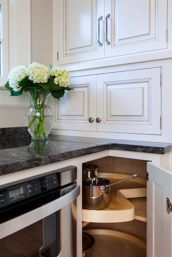 Kitchen - large transitional u-shaped medium tone wood floor kitchen idea in Charlotte with raised-panel cabinets, white cabinets, white backsplash, subway tile backsplash, stainless steel appliances, a double-bowl sink and marble countertops