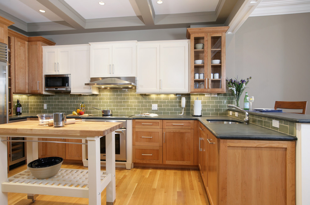 Elegant u-shaped kitchen photo in Boston with shaker cabinets, medium tone wood cabinets, green backsplash, subway tile backsplash, stainless steel appliances and an undermount sink
