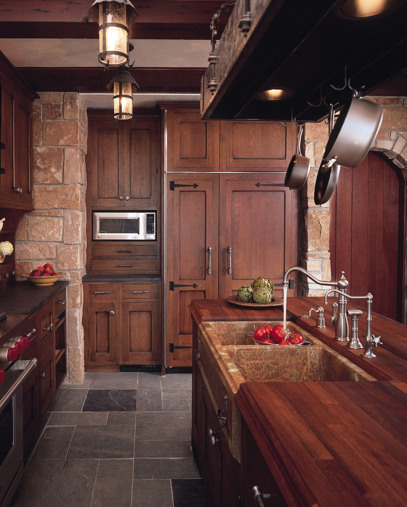 Inspiration for a timeless kitchen remodel in Minneapolis with a farmhouse sink, recessed-panel cabinets, dark wood cabinets and wood countertops