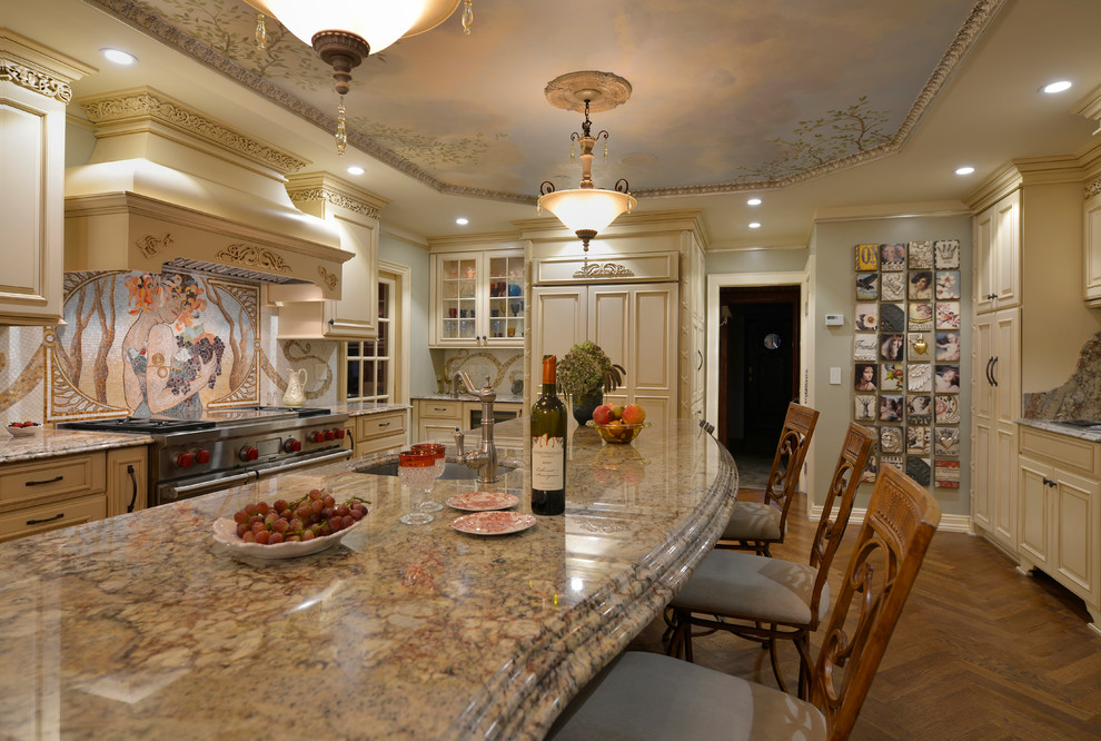 Inspiration for a large timeless l-shaped light wood floor eat-in kitchen remodel in New York with granite countertops, a farmhouse sink, raised-panel cabinets, beige cabinets, multicolored backsplash, mosaic tile backsplash, stainless steel appliances and an island