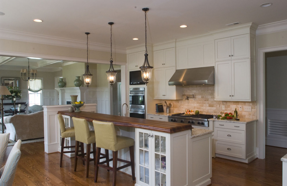 Example of a classic open concept kitchen design in Raleigh with shaker cabinets, wood countertops, white cabinets, beige backsplash and subway tile backsplash