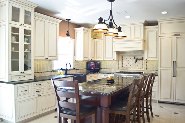 Traditional kitchen with white painted cabinets with ...
