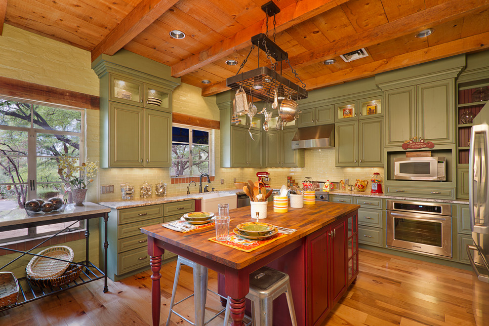 Example of a classic u-shaped kitchen design in Phoenix with a farmhouse sink, raised-panel cabinets, green cabinets, wood countertops, beige backsplash and stainless steel appliances
