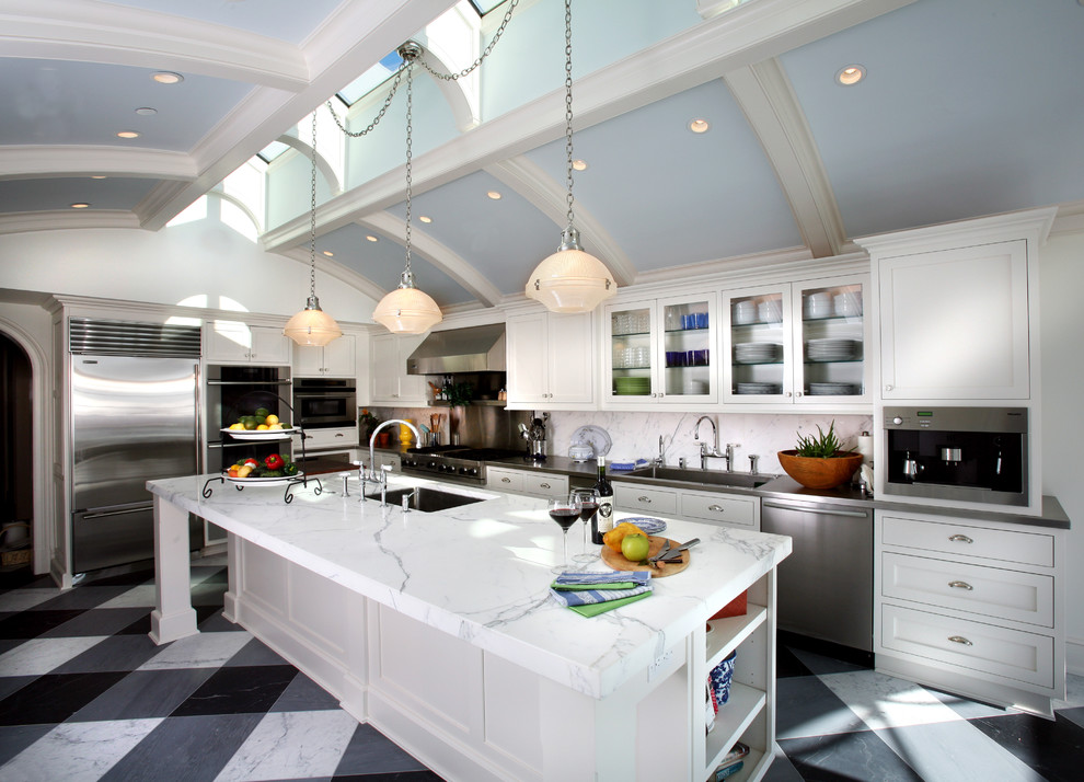Example of a classic l-shaped kitchen design in Newark with glass-front cabinets, stainless steel appliances, a single-bowl sink, white cabinets, white backsplash and stone slab backsplash
