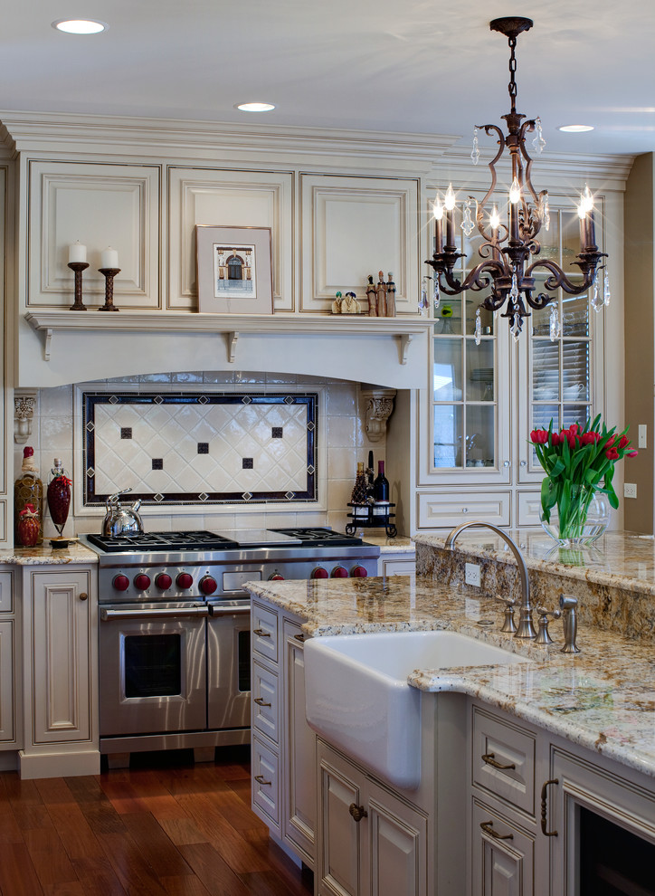 Example of a classic kitchen design in Chicago with a farmhouse sink, raised-panel cabinets, beige cabinets, beige backsplash and stainless steel appliances