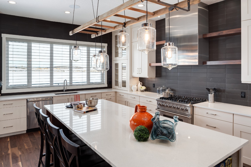 Example of a transitional l-shaped medium tone wood floor kitchen design in Calgary with an undermount sink, black backsplash, stainless steel appliances and an island