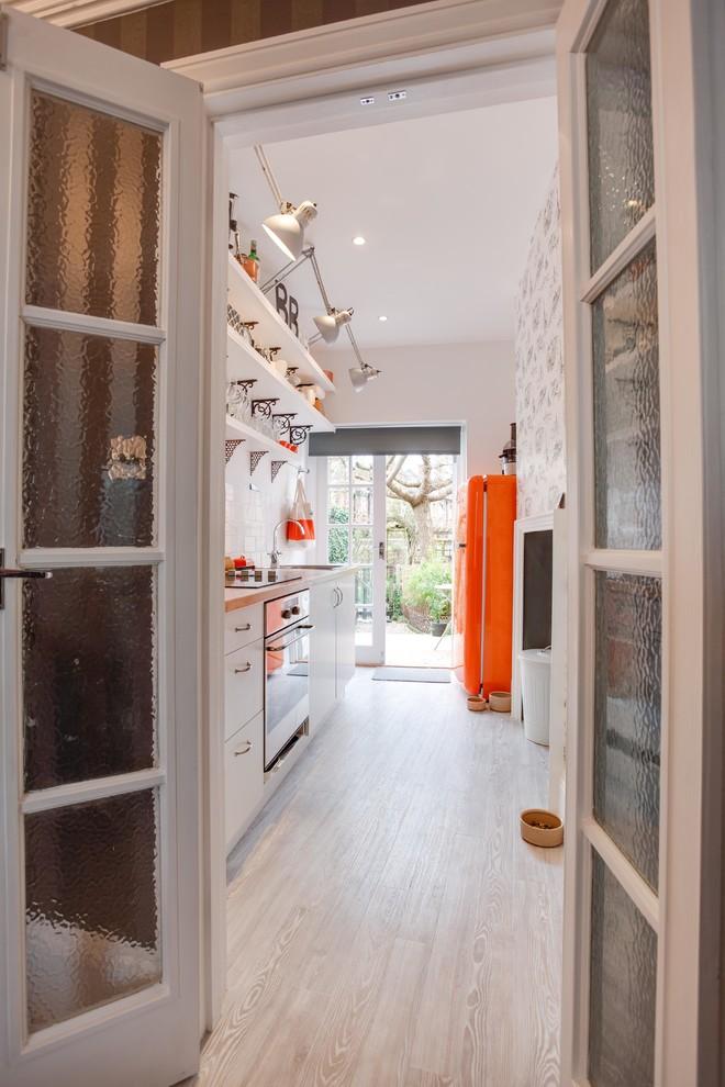 Esempio di una cucina con lavello da incasso, ante lisce, ante bianche, top in legno, paraspruzzi bianco, paraspruzzi con piastrelle in ceramica, elettrodomestici in acciaio inossidabile e pavimento in legno verniciato