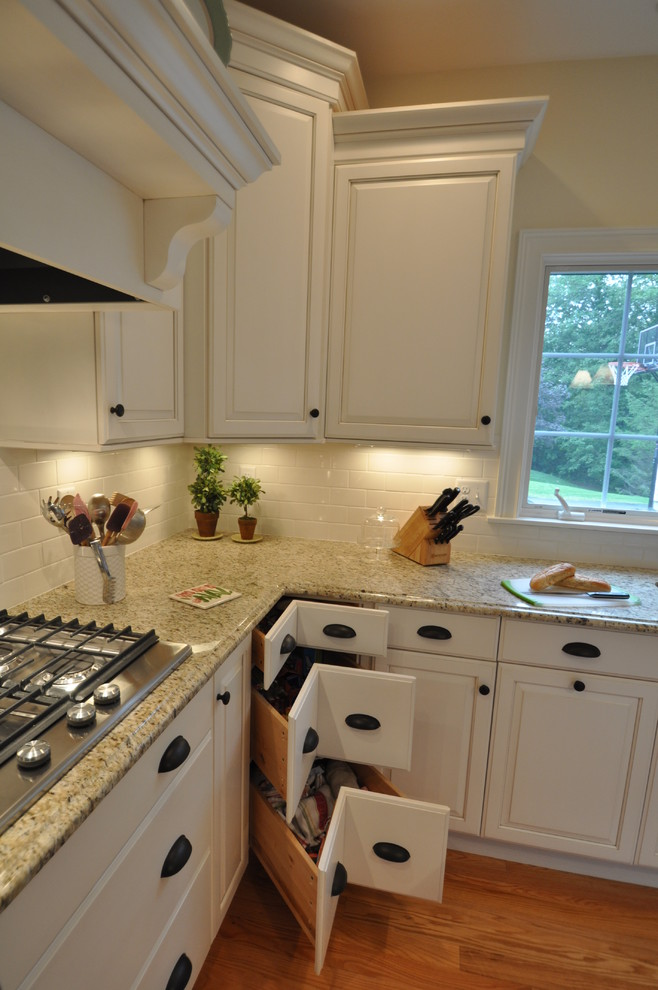 Example of a mid-sized classic medium tone wood floor kitchen design in Boston with an undermount sink, raised-panel cabinets, white cabinets, granite countertops, beige backsplash, subway tile backsplash, stainless steel appliances and an island