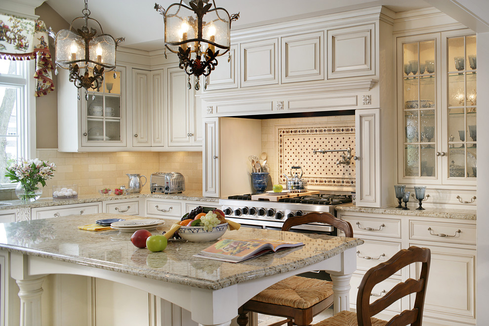 Elegant kitchen photo in New York with raised-panel cabinets, beige cabinets, beige backsplash and stainless steel appliances