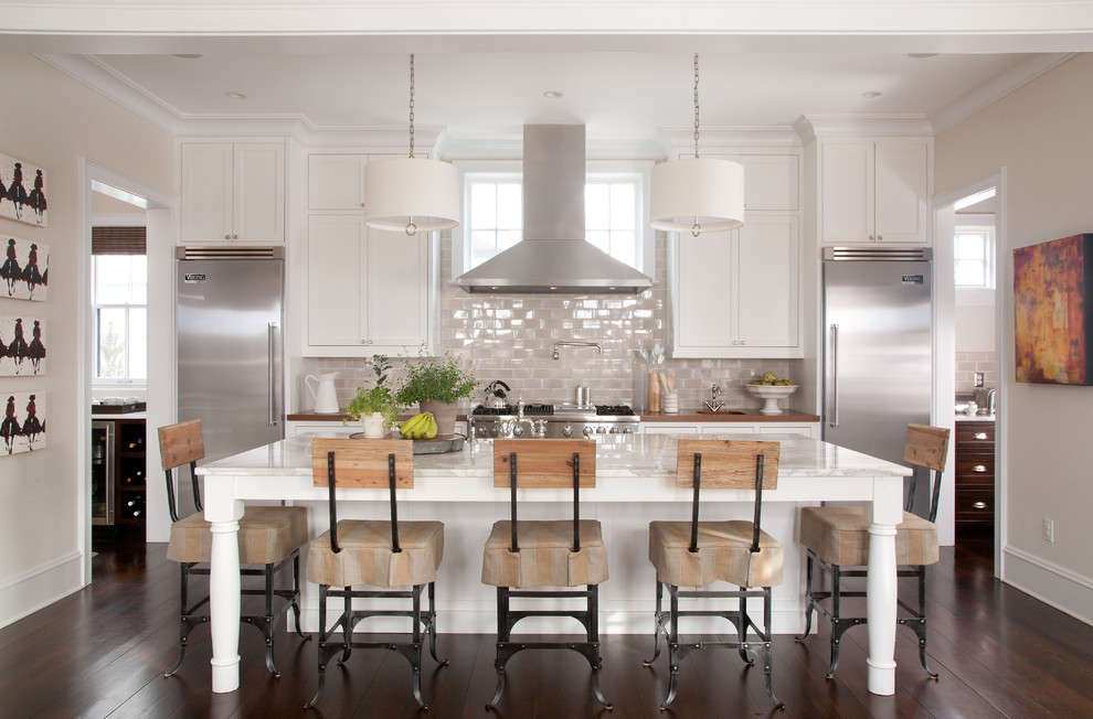 Elegant galley kitchen photo in Denver with stainless steel appliances, marble countertops, recessed-panel cabinets, white cabinets and glass tile backsplash