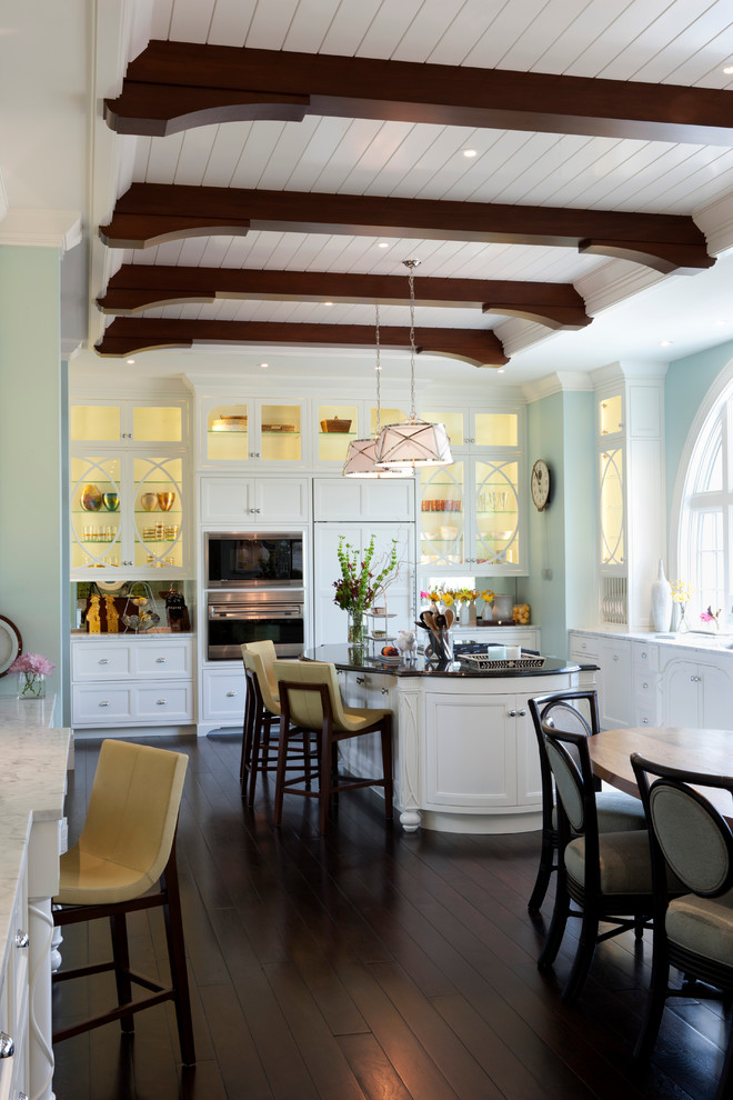 Inspiration for a transitional eat-in kitchen remodel in New York with glass-front cabinets, paneled appliances and white cabinets