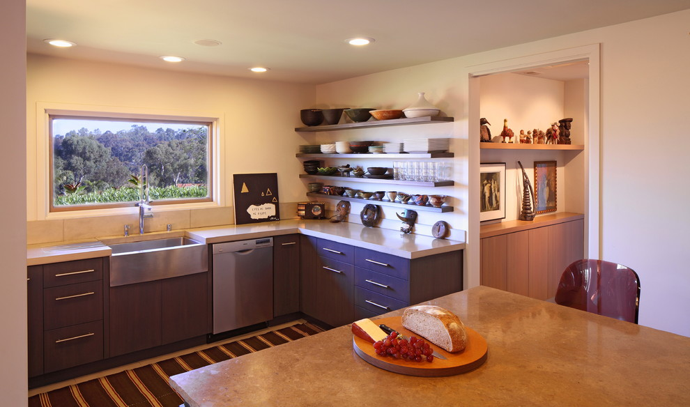 Eat-in kitchen - mediterranean eat-in kitchen idea in Los Angeles with a farmhouse sink, stainless steel appliances, flat-panel cabinets, dark wood cabinets, beige backsplash and no island