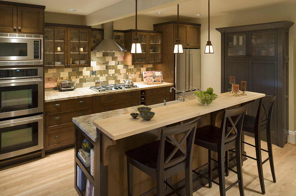 Inspiration for a timeless galley kitchen remodel in Portland with glass-front cabinets, stainless steel appliances, granite countertops, dark wood cabinets and multicolored backsplash