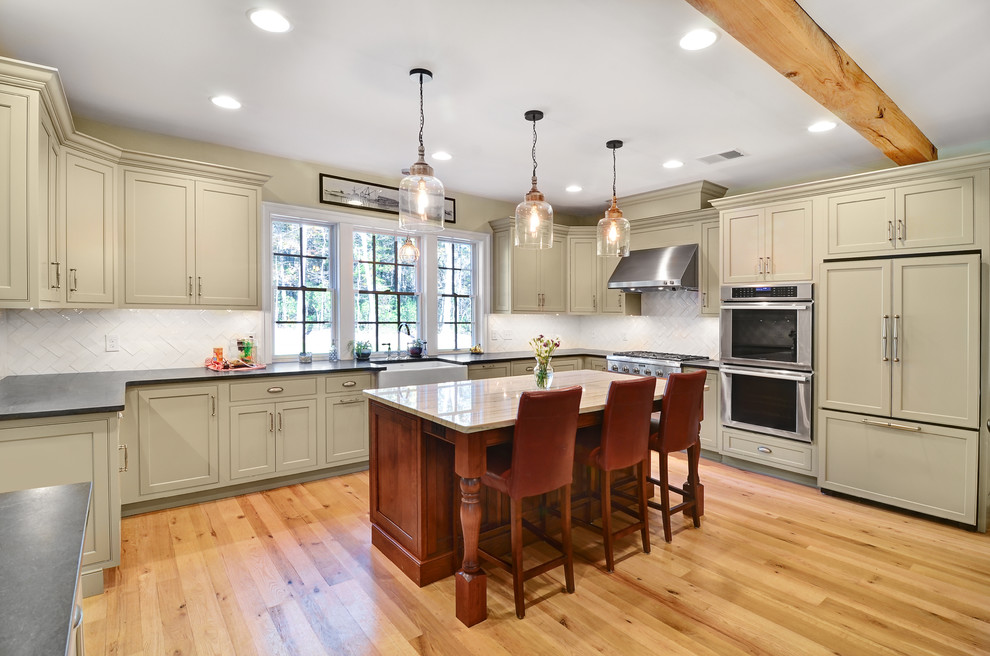 Large cottage u-shaped brown floor and light wood floor kitchen photo in Baltimore with a farmhouse sink, shaker cabinets, beige cabinets, white backsplash, an island, soapstone countertops, glass tile backsplash and paneled appliances