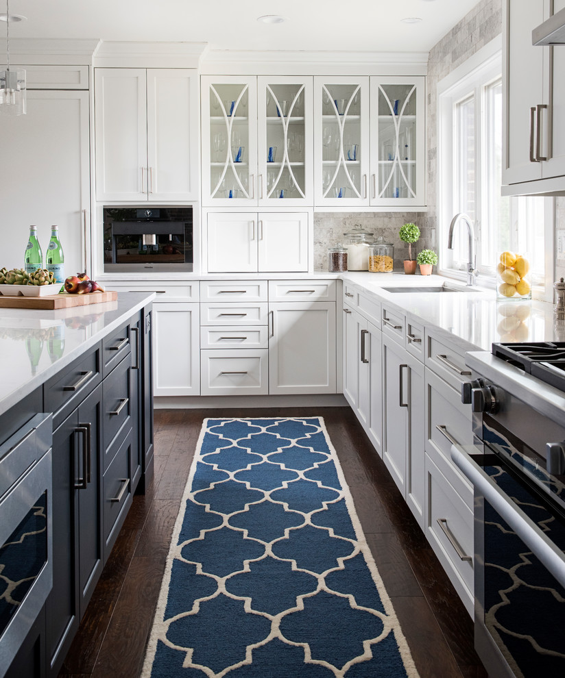 Inspiration for a large transitional l-shaped dark wood floor and brown floor eat-in kitchen remodel in Other with white cabinets, quartz countertops, gray backsplash, stainless steel appliances, an island, an undermount sink, shaker cabinets and stone tile backsplash