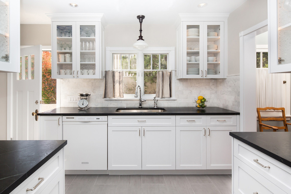 Example of a mid-sized farmhouse galley ceramic tile enclosed kitchen design in Los Angeles with a double-bowl sink, shaker cabinets, white cabinets, soapstone countertops, stone tile backsplash, stainless steel appliances, no island and white backsplash
