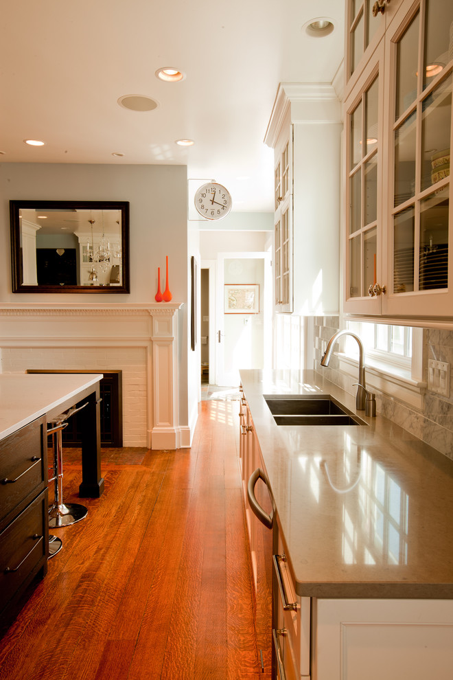 Mid-sized elegant u-shaped medium tone wood floor eat-in kitchen photo in Chicago with glass-front cabinets, a double-bowl sink, quartz countertops, white cabinets, gray backsplash, stainless steel appliances and an island