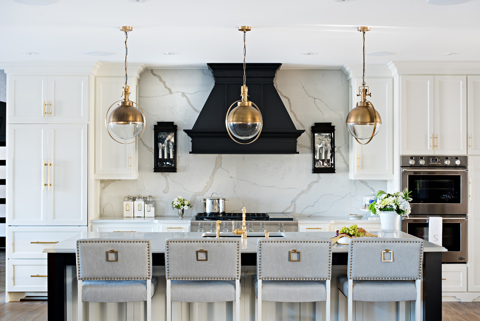 Inspiration for a transitional l-shaped medium tone wood floor open concept kitchen remodel in Toronto with an undermount sink, shaker cabinets, white cabinets, marble countertops, white backsplash, stone slab backsplash, stainless steel appliances and an island
