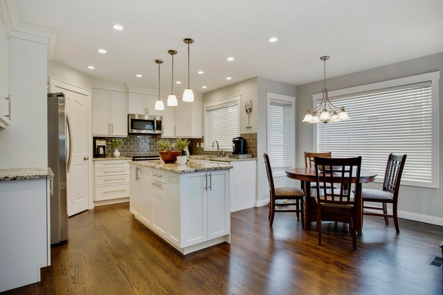 Example of a small transitional u-shaped dark wood floor enclosed kitchen design in Calgary with an undermount sink, shaker cabinets, white cabinets, granite countertops, gray backsplash, porcelain backsplash, stainless steel appliances and an island