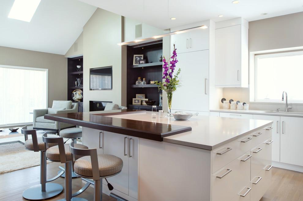 Diseño de cocinas en L clásica renovada, grande, con una isla, fregadero bajoencimera, armarios con paneles lisos, puertas de armario blancas y suelo de madera en tonos medios