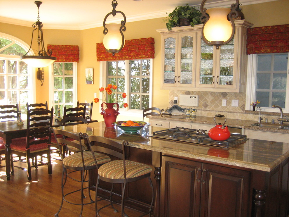 Example of a classic eat-in kitchen design in Los Angeles with glass-front cabinets, beige cabinets and beige backsplash
