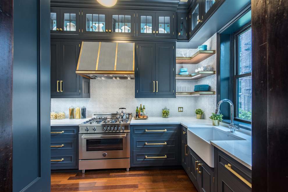 Inspiration for a transitional l-shaped medium tone wood floor and brown floor enclosed kitchen remodel in New York with a farmhouse sink, shaker cabinets, blue cabinets, gray backsplash, stainless steel appliances and no island