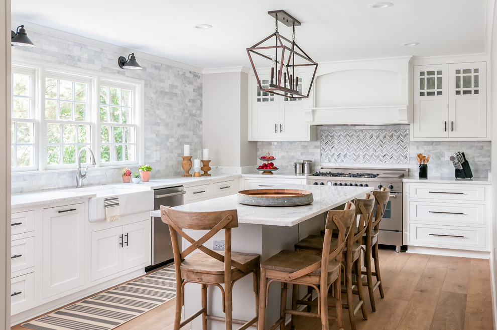 Example of a transitional l-shaped medium tone wood floor kitchen design in Atlanta with a farmhouse sink, shaker cabinets, white cabinets, multicolored backsplash, stainless steel appliances, an island and white countertops