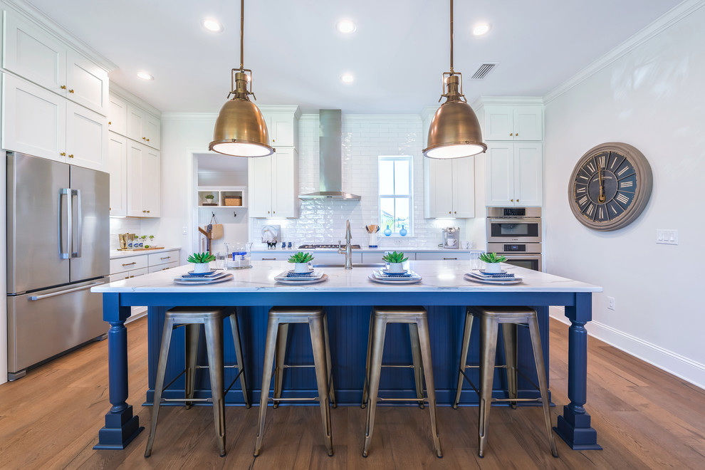 Inspiration for a large transitional u-shaped kitchen remodel in Jacksonville with shaker cabinets, white cabinets, white backsplash, subway tile backsplash, stainless steel appliances and an island