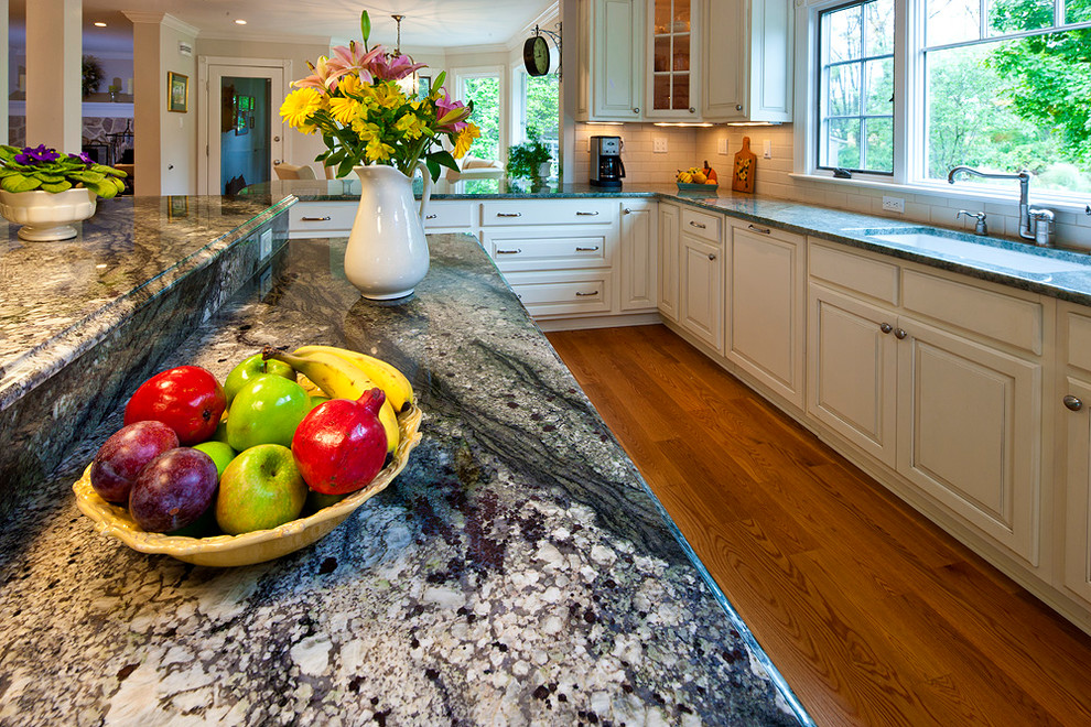 Inspiration for a transitional u-shaped medium tone wood floor eat-in kitchen remodel in Philadelphia with an undermount sink, raised-panel cabinets, green cabinets, granite countertops, beige backsplash, stone tile backsplash and stainless steel appliances