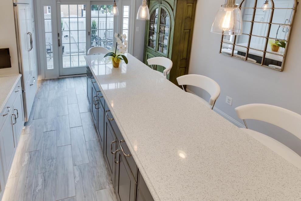 Kitchen - large transitional l-shaped kitchen idea in DC Metro with an undermount sink, raised-panel cabinets, quartz countertops, green backsplash, subway tile backsplash and an island