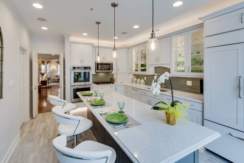 Large transitional l-shaped kitchen photo in DC Metro with an undermount sink, raised-panel cabinets, quartz countertops, green backsplash, subway tile backsplash and an island