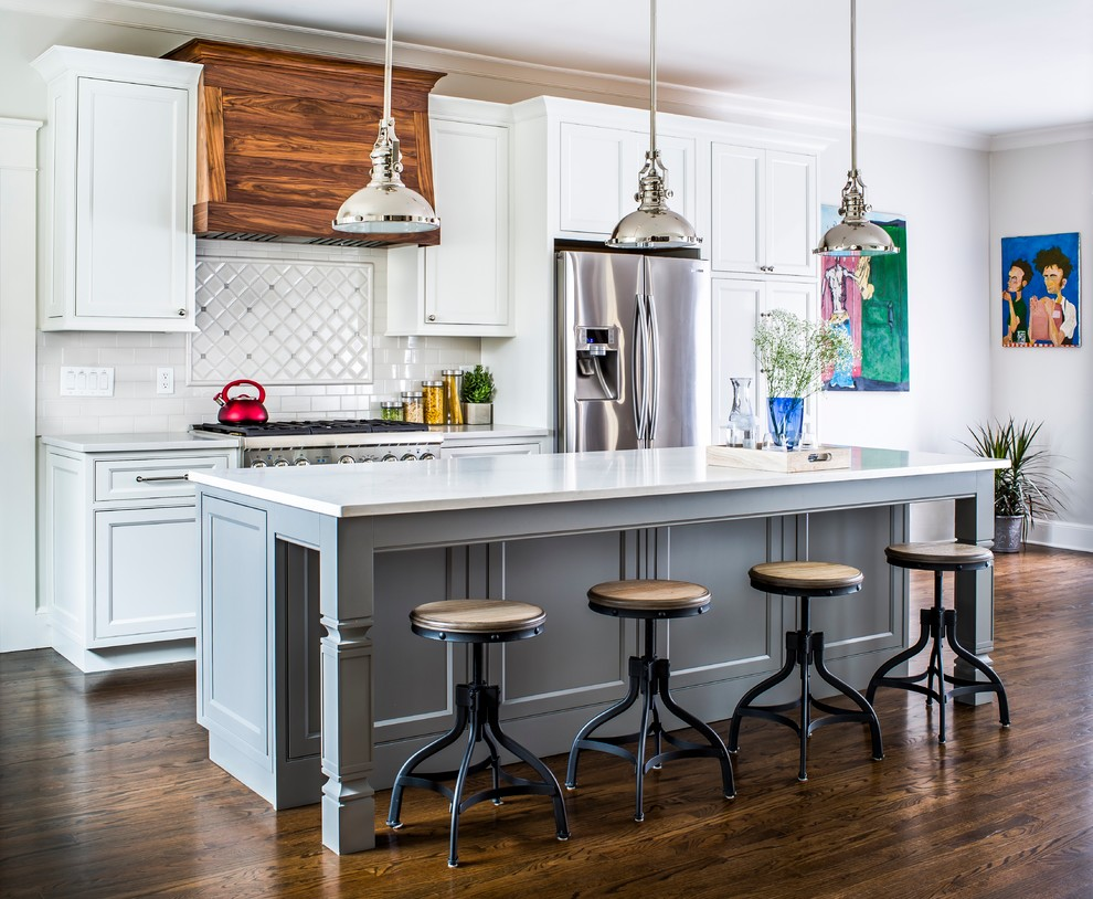 Transitional galley dark wood floor open concept kitchen photo in Philadelphia with recessed-panel cabinets, white cabinets, white backsplash, stainless steel appliances and an island