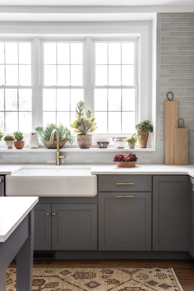 Kitchen - large transitional l-shaped medium tone wood floor and brown floor kitchen idea in Boston with gray backsplash, ceramic backsplash, an island, white countertops, a farmhouse sink, shaker cabinets and gray cabinets
