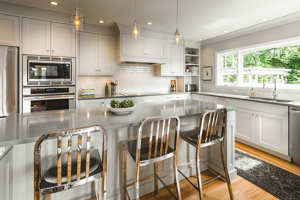 Inspiration for a mid-sized transitional l-shaped medium tone wood floor eat-in kitchen remodel in Vancouver with a double-bowl sink, shaker cabinets, gray cabinets, quartz countertops, white backsplash, stainless steel appliances, an island and ceramic backsplash