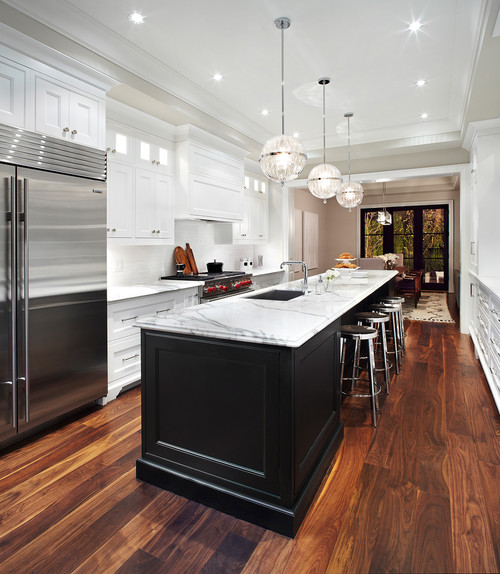 White kitchen design with a long black kitchen island with bar stool seating.