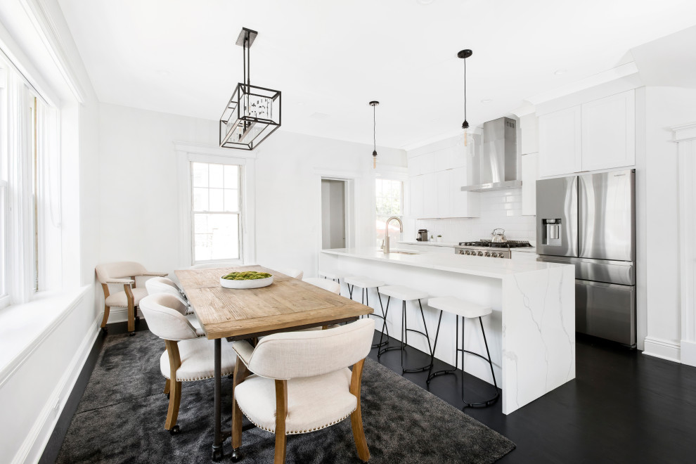Inspiration for a mid-sized transitional single-wall painted wood floor and black floor eat-in kitchen remodel in New York with an undermount sink, shaker cabinets, white cabinets, white backsplash, subway tile backsplash, stainless steel appliances, an island and white countertops