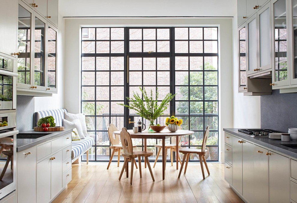 Inspiration for a mid-sized transitional galley medium tone wood floor eat-in kitchen remodel in New York with glass-front cabinets, white cabinets, gray backsplash, no island, solid surface countertops, stone slab backsplash, stainless steel appliances, an undermount sink and gray countertops